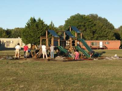 volunteers spreading bedding around playground